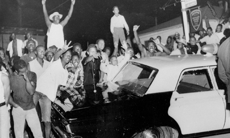 Demonstrators push against a police car after rioting erupted in a crowd of 1,500 in the Los Angeles area of Watts.  14,000 national guardsmen were called in to disperse the rioting and over 100 square blocks were destroyed by arson.